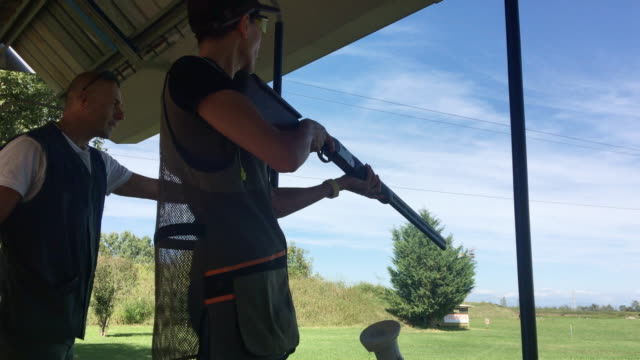 stockvideo's en b-roll-footage met mid adult vrouw oefenen skeet schieten op schieten bereik met instructeur - jachtgeweer