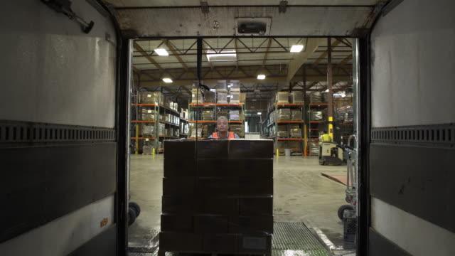 vídeos y material grabado en eventos de stock de mid adult woman pushing out boxes from a warehouse - paleta herramientas industriales