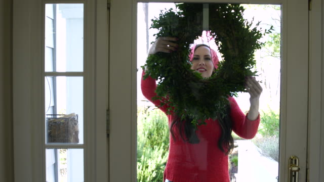mid adult woman putting a wreath on a door - リース点の映像素材/bロール