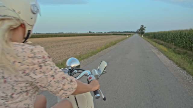 slo mo mid adult woman riding a scooter on country road at dusk - motorcycle stock videos & royalty-free footage
