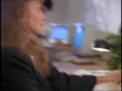 a mid adult woman talking on phone and working on computer in office with other people - other stock videos & royalty-free footage