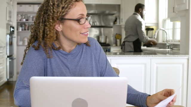 mid adult woman using a laptop in a kitchen - genderblend video stock e b–roll