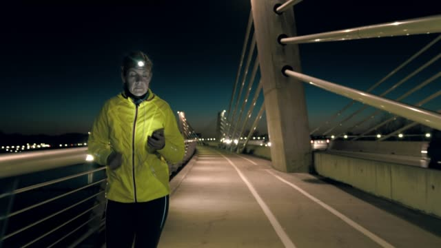 slo mo mid adult woman using a smartphone while jogging across the bridge - headlight stock videos & royalty-free footage