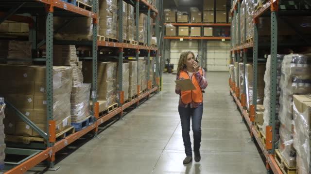 vídeos y material grabado en eventos de stock de mid adult woman using a walkie-talkie in a warehouse - walkie talkie