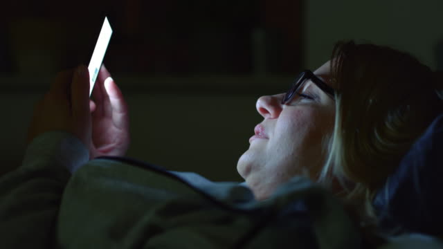 ms mid adult woman using her smartphone at night - herpes video stock e b–roll