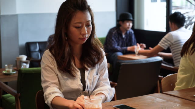 mid adult woman using smart phone at cafe - foodie stock videos and b-roll footage