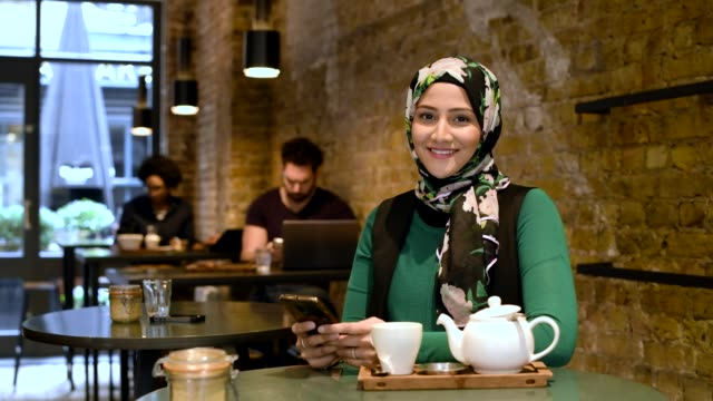 mid adult woman using smartphone in cafe and smiling - hijab stock videos and b-roll footage