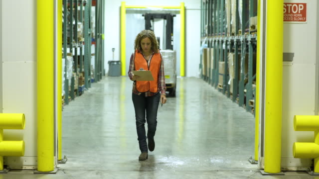 mid adult woman walking in a warehouse - weitwinkelaufnahme stock-videos und b-roll-filmmaterial