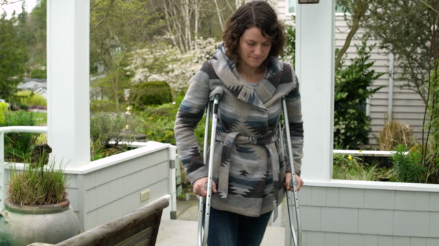 Mid adult woman walking with crutches on a porch