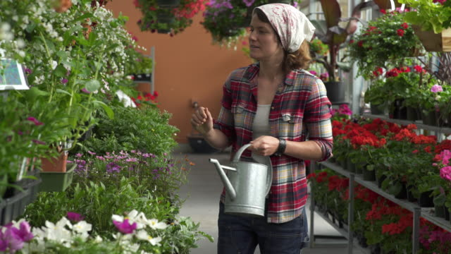 Mid adult woman watering flowers in a greenhouse