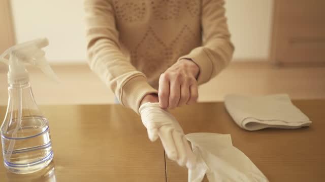 vídeos y material grabado en eventos de stock de la mujer adulta mediana usa guantes de nitrilo para esterilizar su sala de estar con alcohol. - una mujer de mediana edad solamente