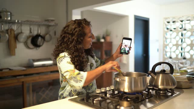 vídeos de stock, filmes e b-roll de mulher adulta média fazendo uma chamada de vídeo no smartphone enquanto cozinhava em casa - film moving image