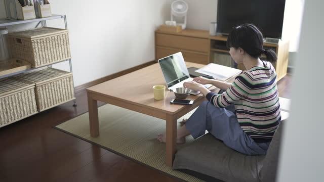 mittlere erwachsene frau arbeiten von zu hause aus und mit einem computer im wohnzimmer. - einzelne frau über 40 stock-videos und b-roll-filmmaterial