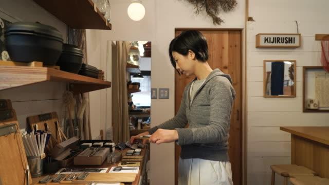 小さな雑貨店で働く 30 代の女性 - 精算カウンター点の映像素材/bロール