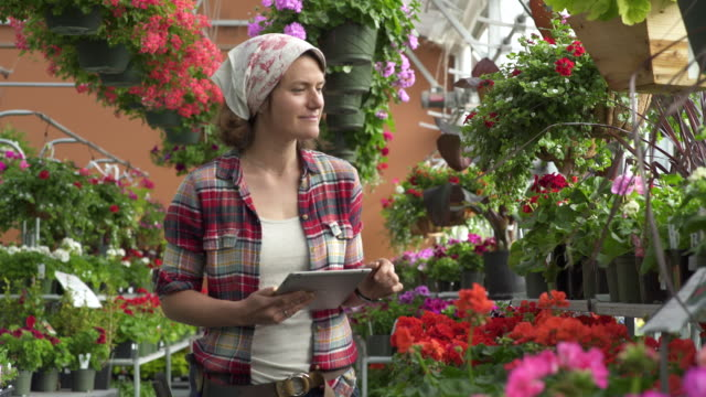 Mid adult woman working with a tablet in a greenhouse