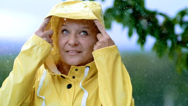 super slo mo mid adult womanin the raincoat enjoying the rain - hood clothing stock videos & royalty-free footage