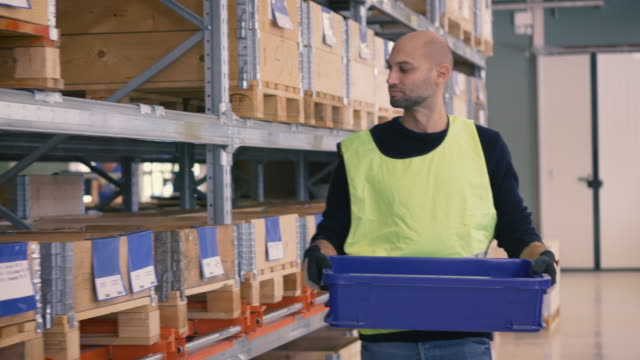 Mid adult worker holding blue crate while walking by rack at warehouse