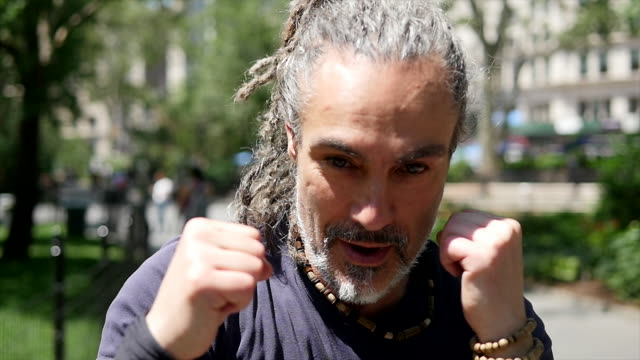 mid age rastafarian man doing martial arts fight boxing training excercise outdoors