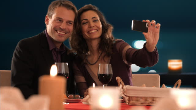 mid aged couple at dinner taking picture - digital camera stock videos and b-roll footage
