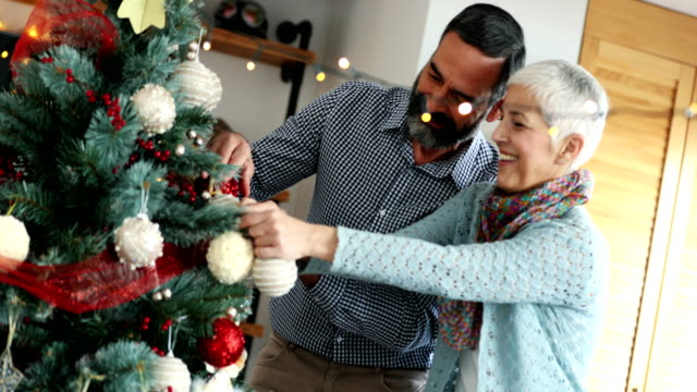 Mid aged couple decorating a Christmas tree.