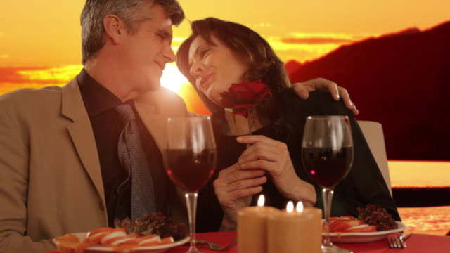 vidéos et rushes de mid aged couple dining in sunset - overexposed