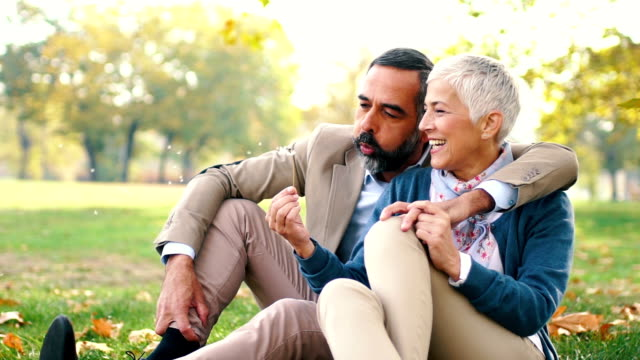 mid aged couple in a park - cinquantenne video stock e b–roll