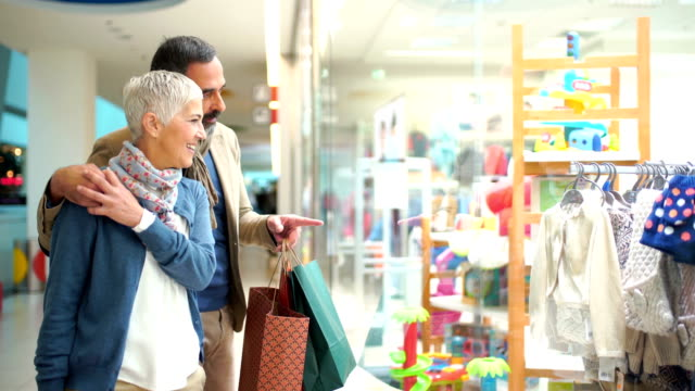 mid aged couple in a shopping mall. - active seniors stock videos & royalty-free footage