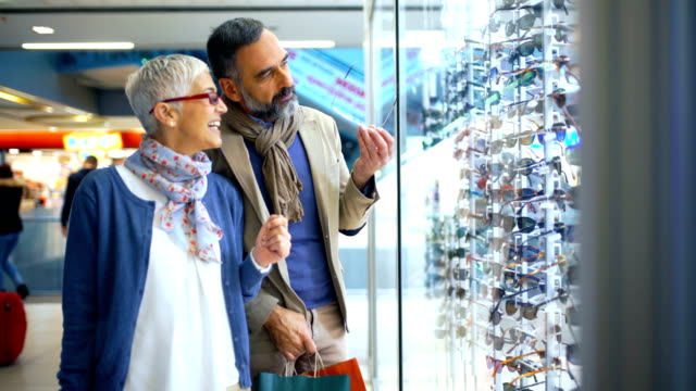 mid aged couple in a shopping mall. - eyeglasses stock videos & royalty-free footage