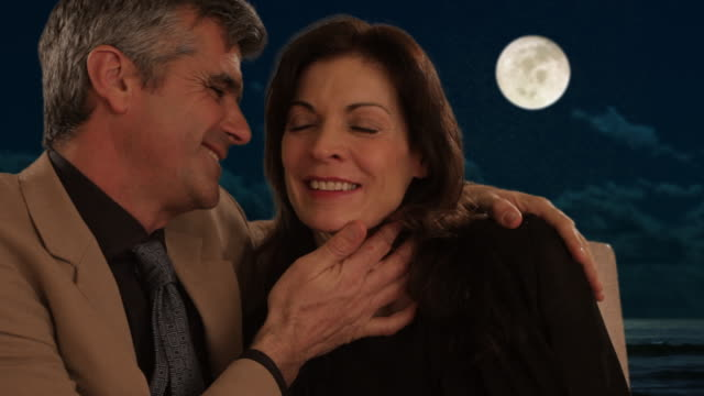 mid aged couple sitting in moonlight