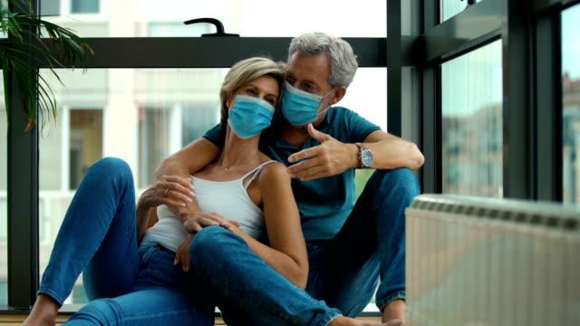 stockvideo's en b-roll-footage met midden verouderd paar dat thuis tijdens coronavirus quarantaine blijft. - op de grond zitten
