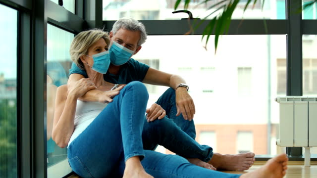 vídeos y material grabado en eventos de stock de pareja de mediana edad que se queda en casa durante la cuarentena del coronavirus. - refugiarse en un lugar concepto