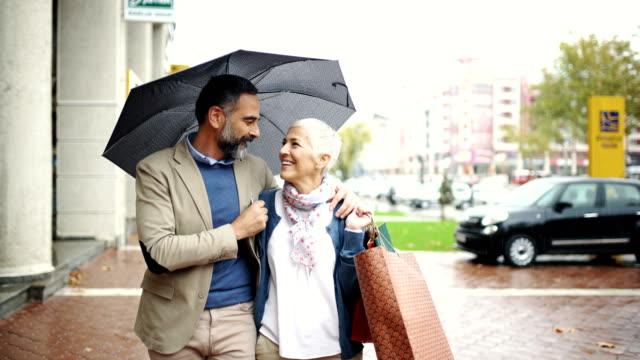 stockvideo's en b-roll-footage met midden leeftijd paar lopen op een regenachtige dag. - mid volwassen