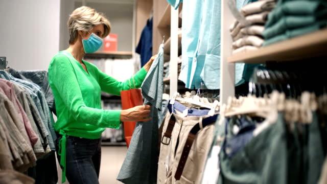 vídeos de stock, filmes e b-roll de mulher de meia idade em um shopping durante o coronavírus. - bolsa objeto manufaturado