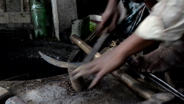Mid close shot of filing of sickle by an Indian  blacksmith.