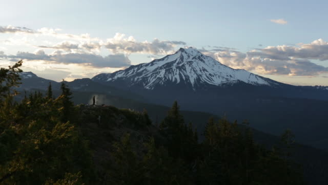 mid distance lockdown shot of person on cliff against snowcapped triangulation peak during sunset - mid distance stock videos & royalty-free footage
