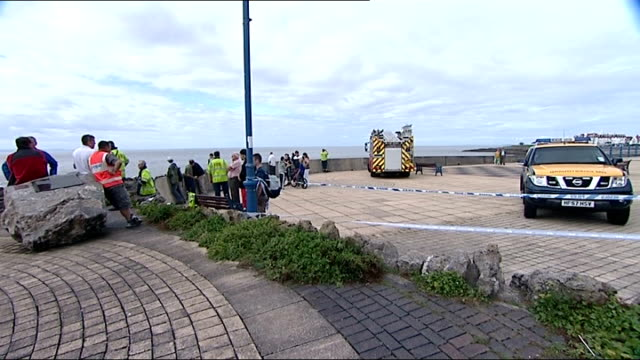 porthcawl: ext area of coast where 13-year-old boy was swept out to sea emergency services workers and vehicles near sea wall lifeboatmen looking out... - mid wales stock videos & royalty-free footage