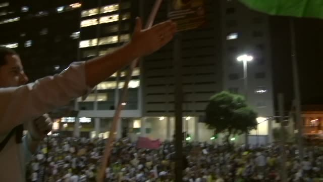 Mid Panning Shot Protest leader on top of double decker truck with Brazil flag on Avenida Presidente Vargas with hundreds of thousands in attendance
