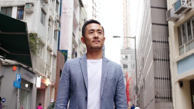 mittleres porträt eines mittleren erwachsenen mannes stand draußen und schaute in die kamera - chinesischer abstammung stock-videos und b-roll-filmmaterial