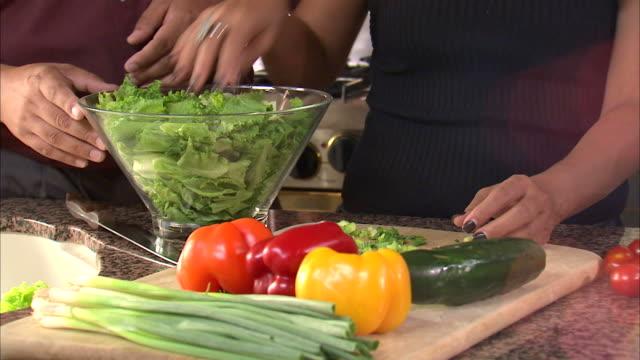 vídeos y material grabado en eventos de stock de cu ds mid section of couple preparing salad in kitchen / orem, utah, usa - orem