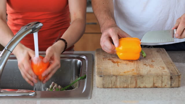 cu mid section of couple washing and cutting vegetables in kitchen, jersey city, new jersey, usa - orangefarbige paprika stock-videos und b-roll-filmmaterial