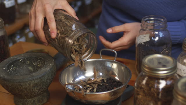 CU HA Mid section of herbalist grinding herbs in mortar and pestle in shop / Manchester, Vermont, USA