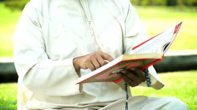 mid section of muslim grandfather read quran in public park in morning - koran stock videos & royalty-free footage
