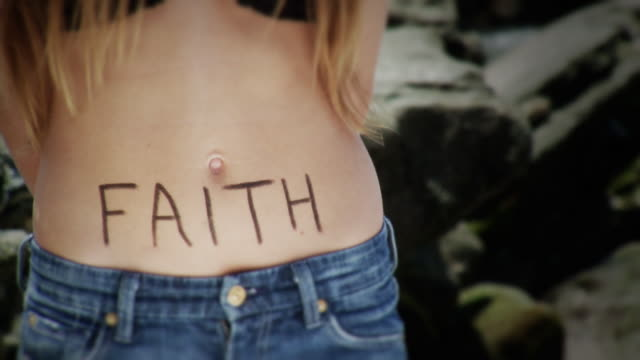 CU Mid section of teenage girl standing by rocks with 'faith' written on belly, Laguna Beach, California, USA