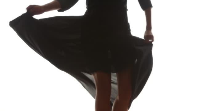 Mid section of woman in black dress dancing on white background