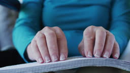 Mid section of woman reading braille book