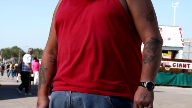 Mid section view of obese man with tattoos