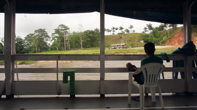 vídeos y material grabado en eventos de stock de mid shot a boy is watching the changing landscape from a moving riverboat a transport riverboat travels in the brazilian amazon from maues to manaus... - amazonas state brazil