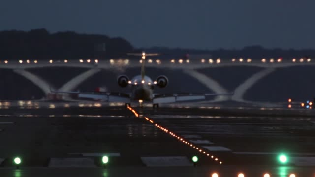 vidéos et rushes de mid shot a commercial jet lands at the runway of reagan national airport followed by another jet to take off from the airport arlington va august 15... - aéroport ronald reagan