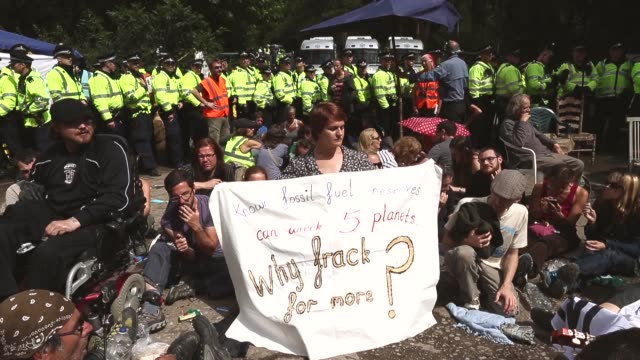 """mid shot, a protestor holding a banner reading """"known fossil fuel reserve can wreck 5 planets. why frack for more"""". protesters gather outside a drill... - west sussex stock videos & royalty-free footage"""