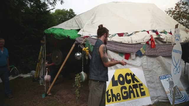 mid shot, a protestor waving a stick. protesters gather outside a drill site operated by cuadrilla resources ltd on august 19, 2013 in balcombe, west... - west sussex stock videos & royalty-free footage